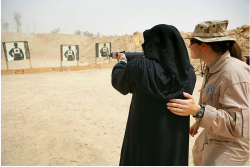 An Iraqi woman practices shooting a weapon under the supervision of International Police Advisor Anna Bailey on a range in Fallujah, Iraq, April 29, 2008.